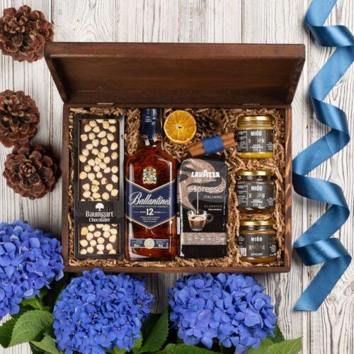 kosz prezentowy z whisky Ballantines 12 Yo, kawą Lavazza i czekoladą w drewnianej skrzyni
